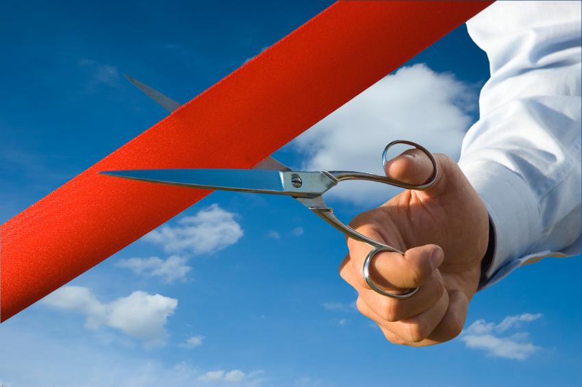 Man cutting a red ribbon